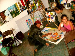 "In the end of 2005 and beginning of 2006 the Col-Art-movement has its ""renais-     sance"" first of all in Tepoztlan, Mexico. On the photo you see painter GALI, inter- vening in the ""Col-Art-painting Tepoztlan"" (35 participants), observed by Sarah Smith, an american painter, and her daugther."